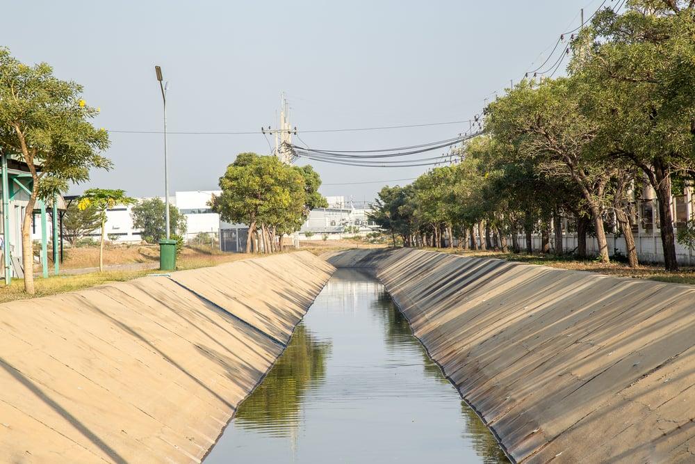 Stormwater runoff flows through concrete drainage system.