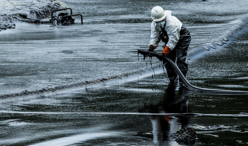 Worker cleans up oil spill