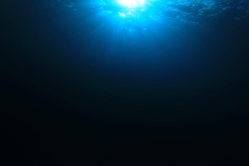 Deep ocean view of sunlight hitting ocean underwater
