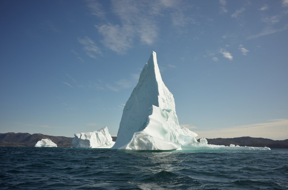 Tall iceberg floats in open water
