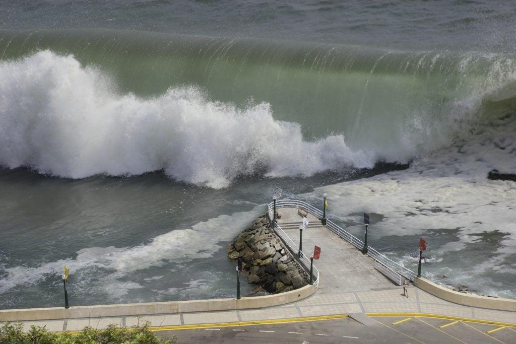 A large wave crashing near a concrete pier.