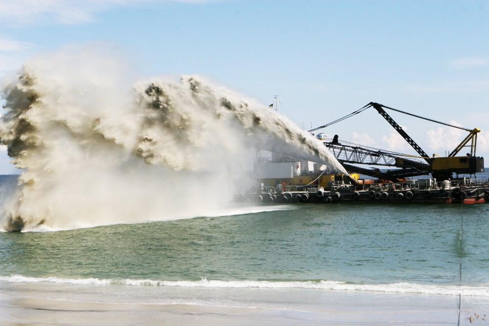 ship dredging sand onto a beach