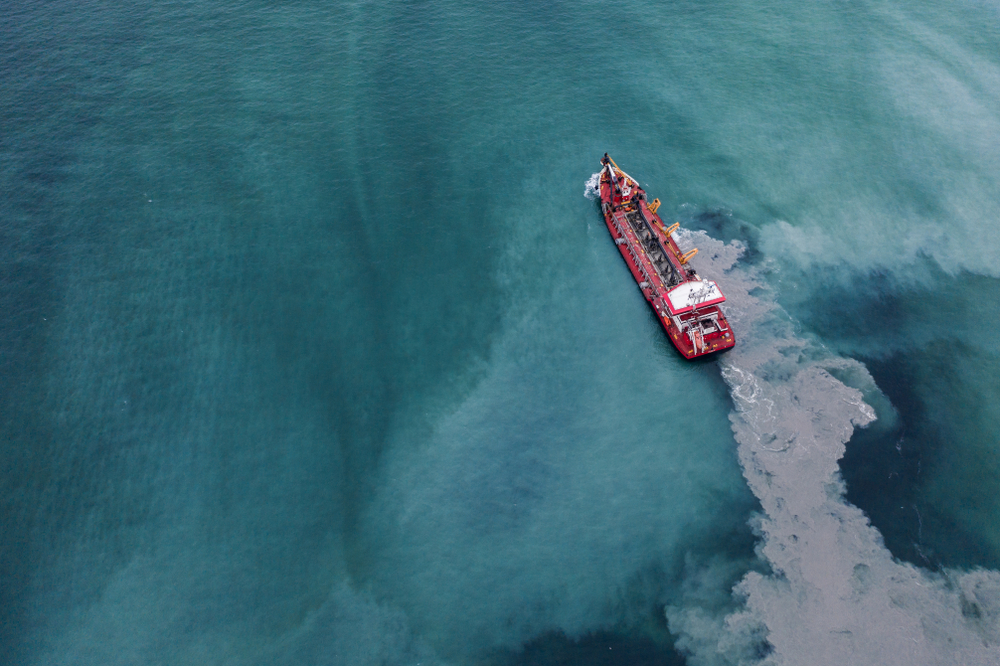 ship dredging the ocean for beach replenishment project